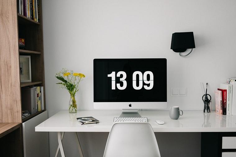 Arredare uno studio, scrivania con computer, vaso con fiori