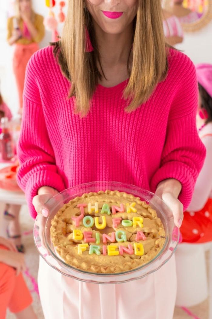 Regalo per un'amica, torta con scritta, donna con maglione rosa