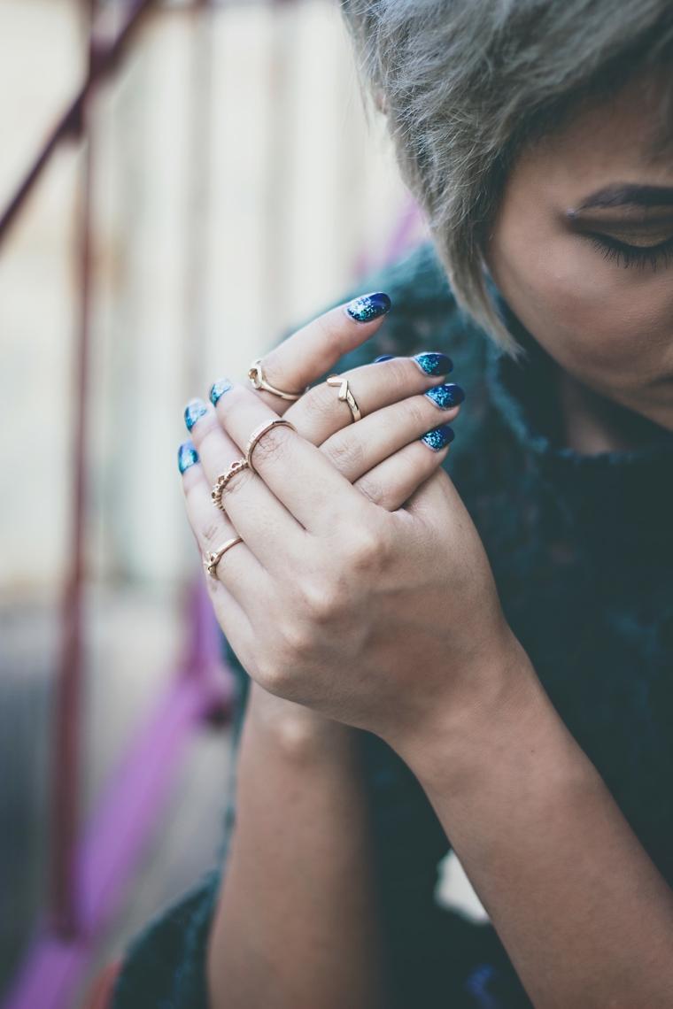 Donna con capelli corti, unghie gel particolati, smalto colore blu
