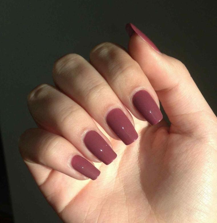 Smalto scuro lucido, unghie lunghe, mano di una donna