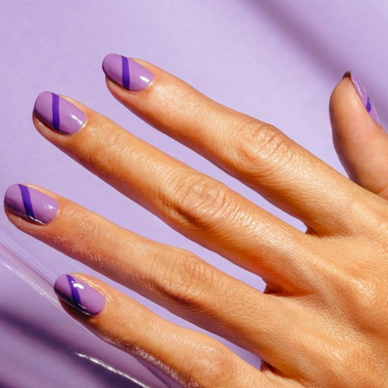 Disegni sulle unghie, smalto lucido viola, mano di donna