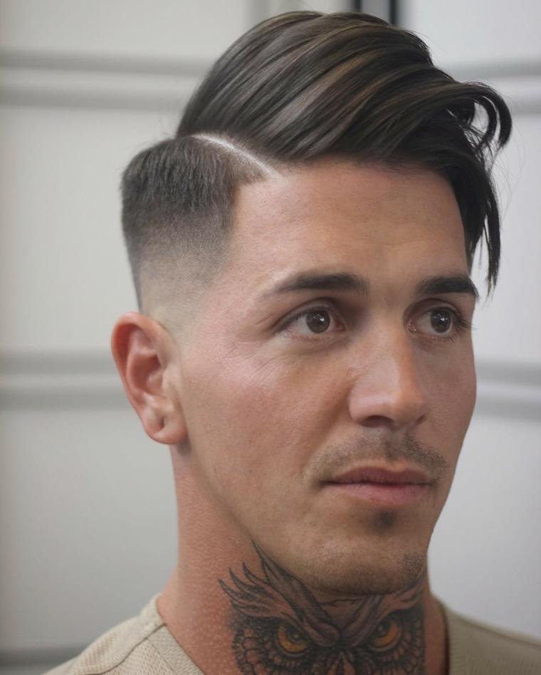 Ragazzo con tatuaggio, capelli rasati lateralmente, acconciatura pompadour