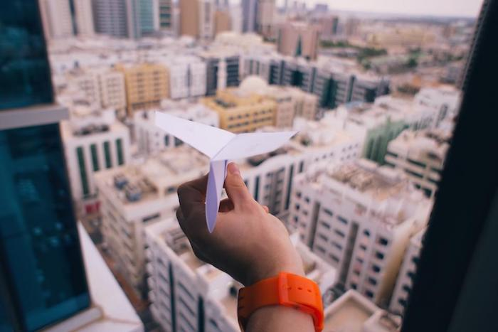 Figurina con aereo di carta, vista di una città wallpaper il computer