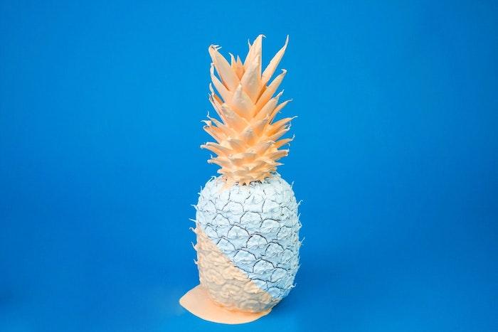 Fotografia di un ananas, ananas colorato, sfondo immagine colore blu