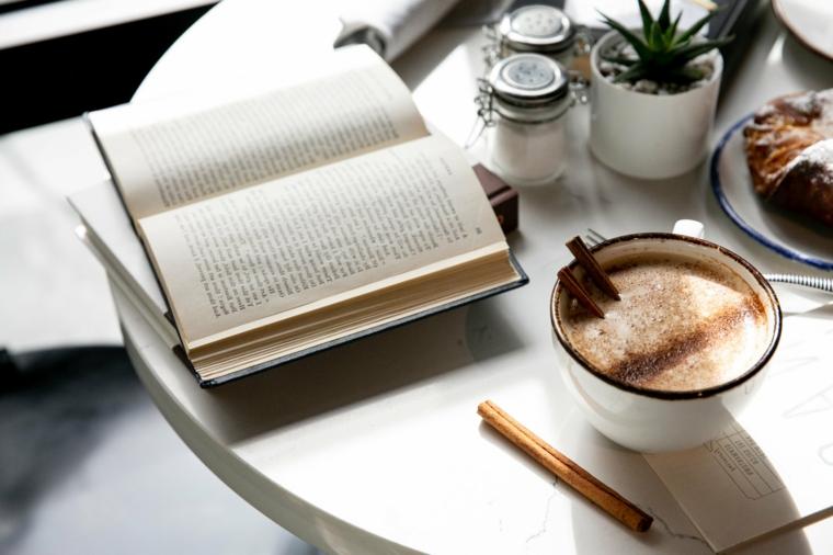 Pensieri che colorano la vita, libro aperto, tazza con cappuccino, bastoncini di cannella
