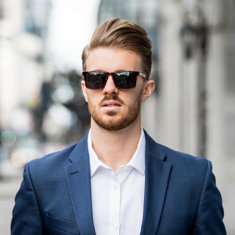Uomo con barba, acconciatura stile pompadour, capelli rasati ai lati