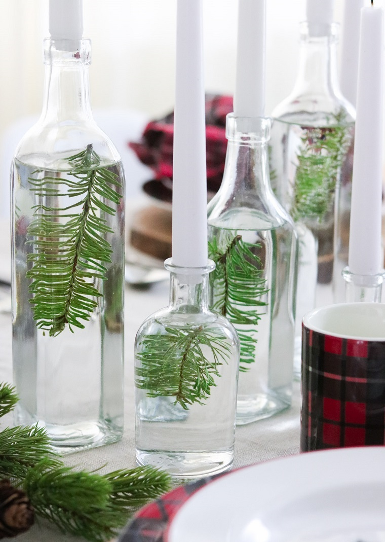 Tavole natalizie, portacandele di vetro, bottiglia con acqua e rametti