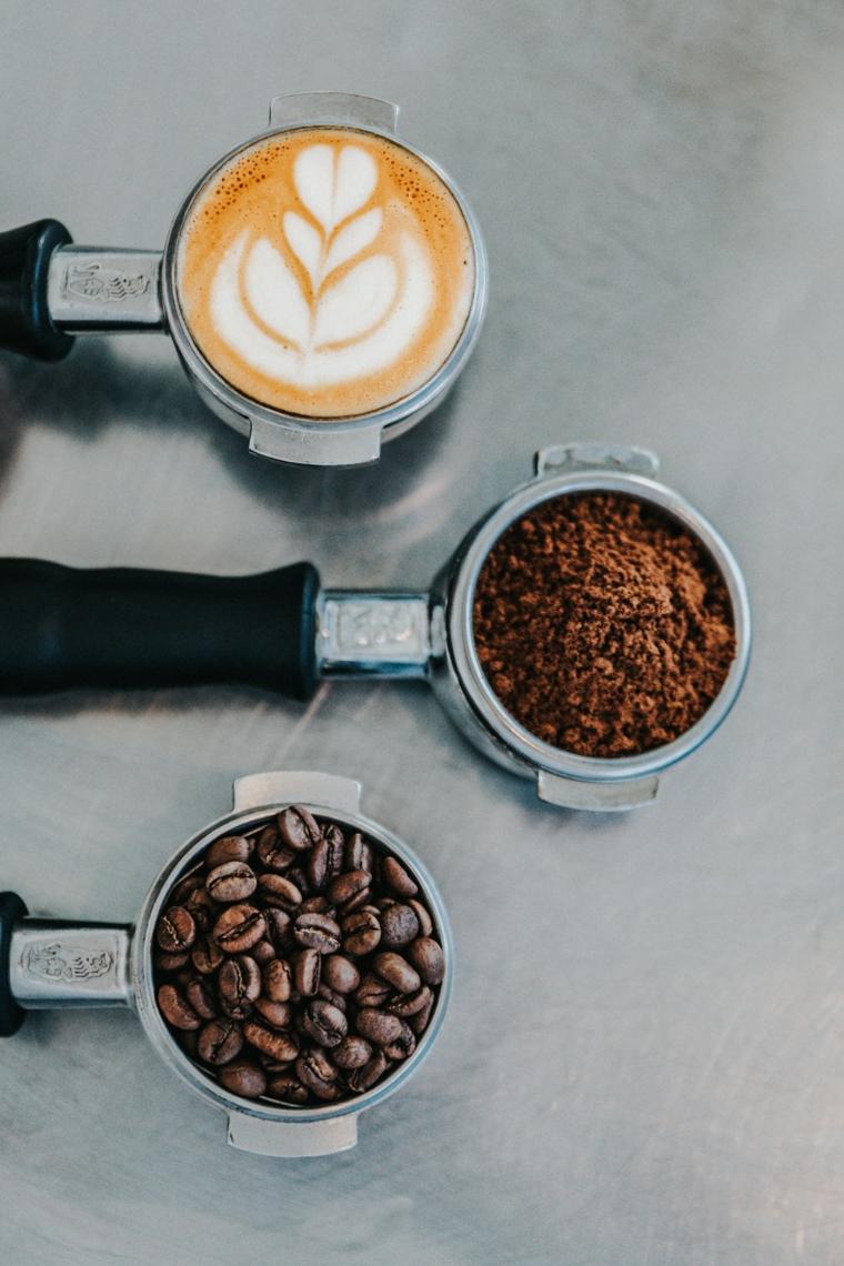 Chicchi di caffè, cappuccino con disegno, polvere di caffè, pensieri che colorano la vita