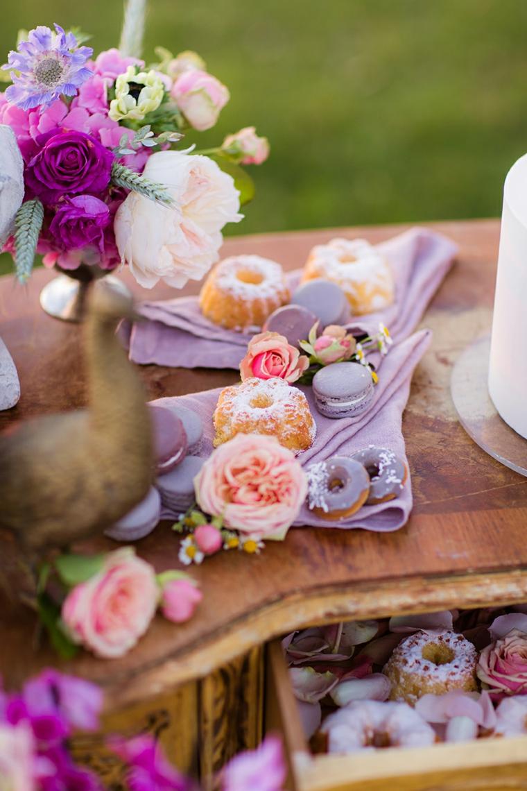 Tavolo con fiori, macaron colorati, colazione con ciambelle