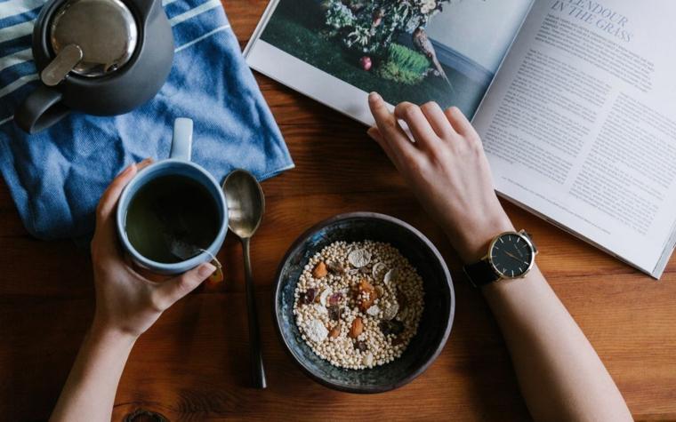 Colazione con musli, tazza con caffè, rivista di viaggi, saluti divertenti