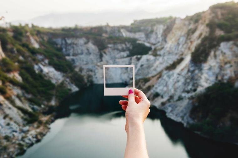 Lago con montagne intorno, filtro di foto, mano di una donna