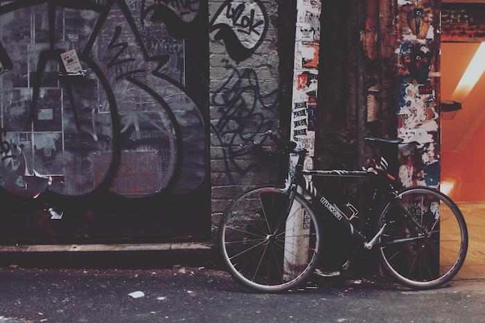 Fotografia di una bicicletta, muro con graffiti, wallpaper telefono