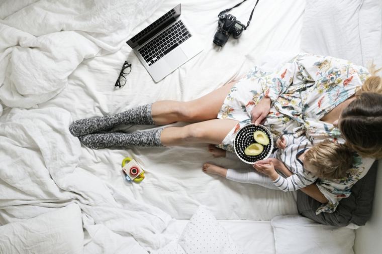 Augurare buona giornata, computer sul letto, piatto con avocado