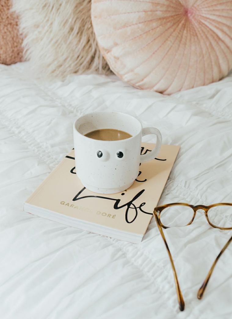 Immagini con frasi significative, tazza di caffè latte, libro e occhiali da vista