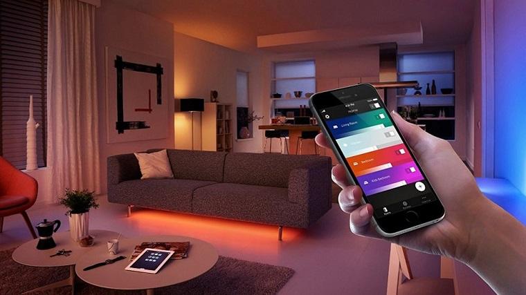 Impianto elettrico domotico, salotto con divano, telefono in mano