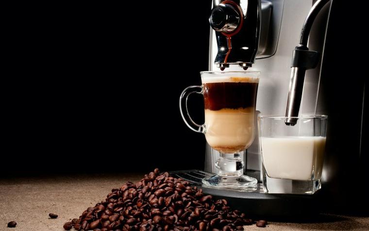 Caffè latte in tazza grande, macchina di caffè, chicchi di caffè
