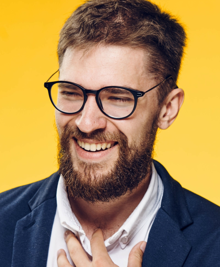 Uomo con barba, occhiali da vista neri, capelli castani mossi