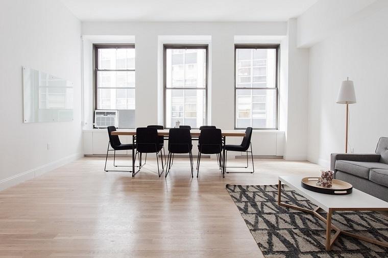Ufficio con tavolo grande, pavimenti in pvc, divano colore grigio, tappeto forme geometriche