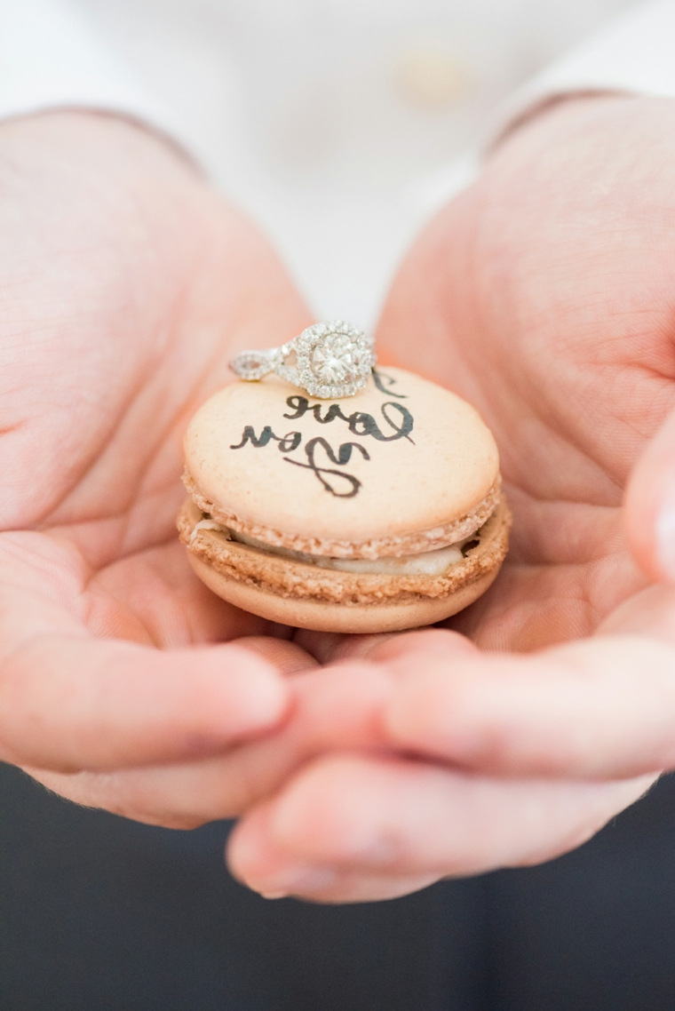 Macaron di colore rosa, anello con diamante, mani di un uomo