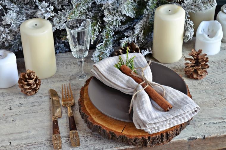 Centrotavola con le pigne, segnaposti con bastoncini di cannella, candele grandi