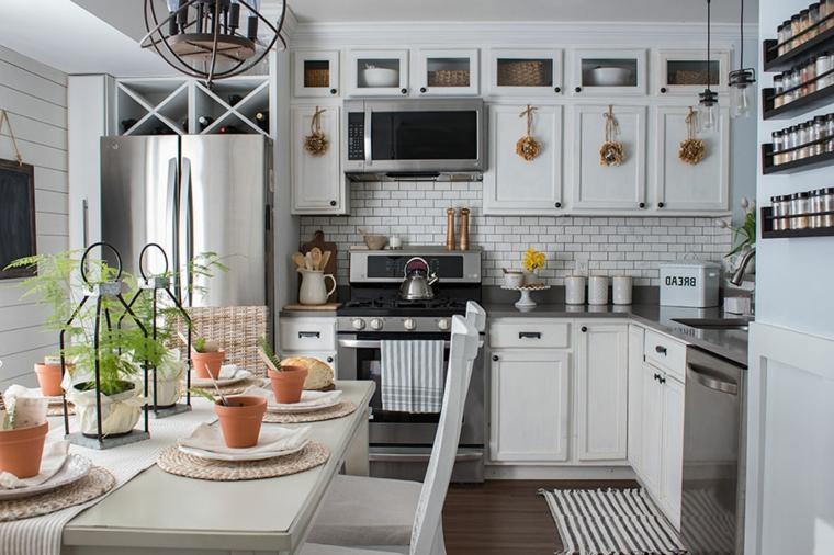Cucina con mobili di legno, tavolo apparecchiato, segnaposto con vasi