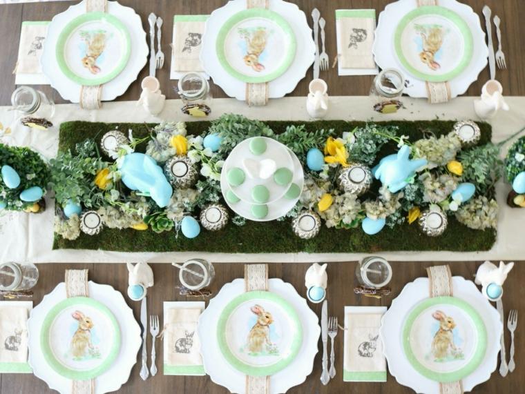 Piatti con coniglietti, centrotavola con uova dipinte, tavola apparecchiata per Pasqua