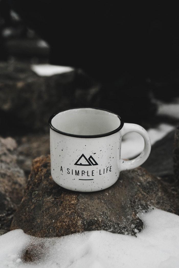 Una tazza di metallo, rocce con neve, sfondo per il telefono