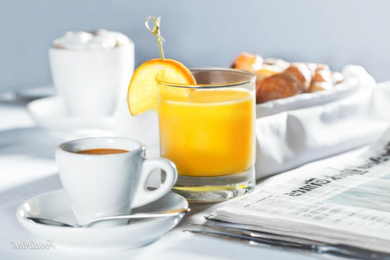 Bicchiere con succo di arancia, tazzina di caffè, foto di buongiorno