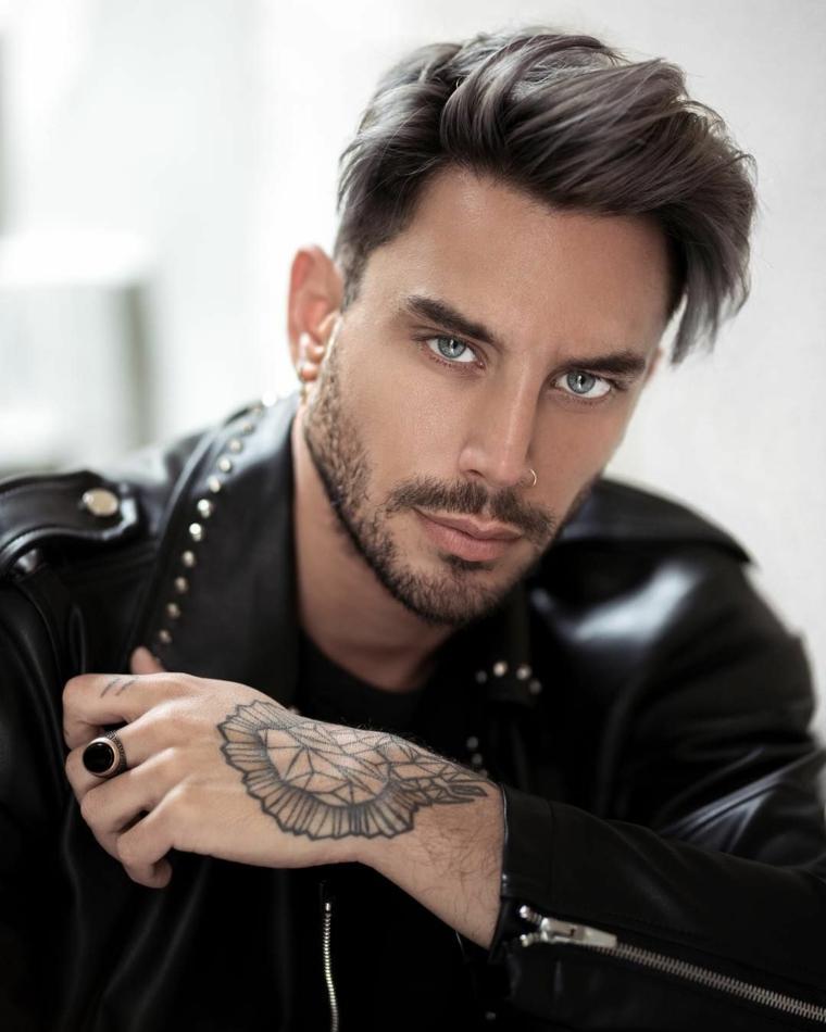 Tatuaggio da uomo sul braccio, giacca di pelle colore nero, acconciatura capelli castani