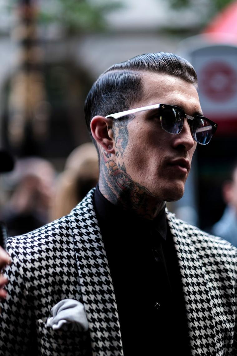 Uomo con tatuaggi, acconciatura con riga laterale, occhiali da sole maschili