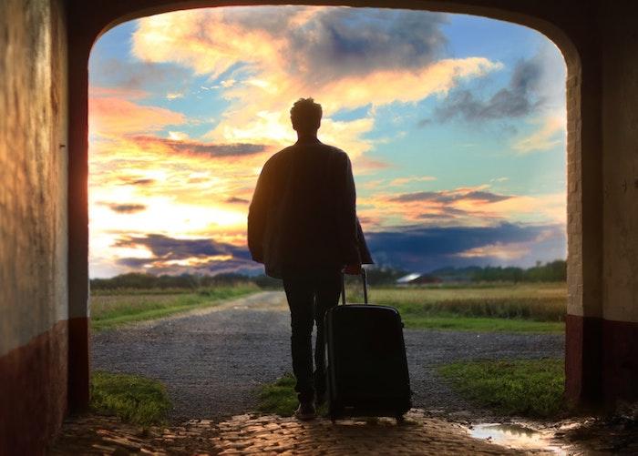 Uomo con valigia, cielo con nuvole, idea sfondo per il computer