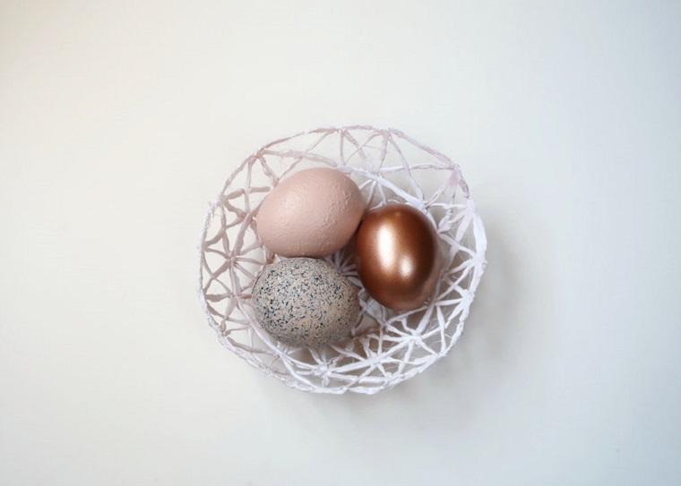 Centrotavola pasquali fai da te, cestino di colla, tre uova dipinte per Pasqua