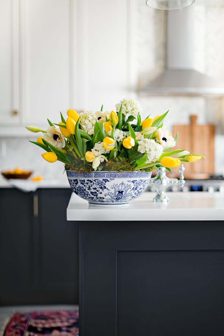 Piatto tondo con fiori, tulipani gialli, cucina con mobili di legno