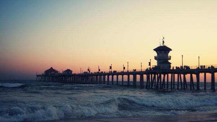 Spiaggia con ponte, il tramonto sul mare, cambiare lo sfondo per il telefono