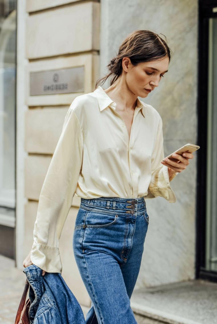 Abbigliamento casual donna, capelli lunghi castani, pettinature semplici, telefono in mano