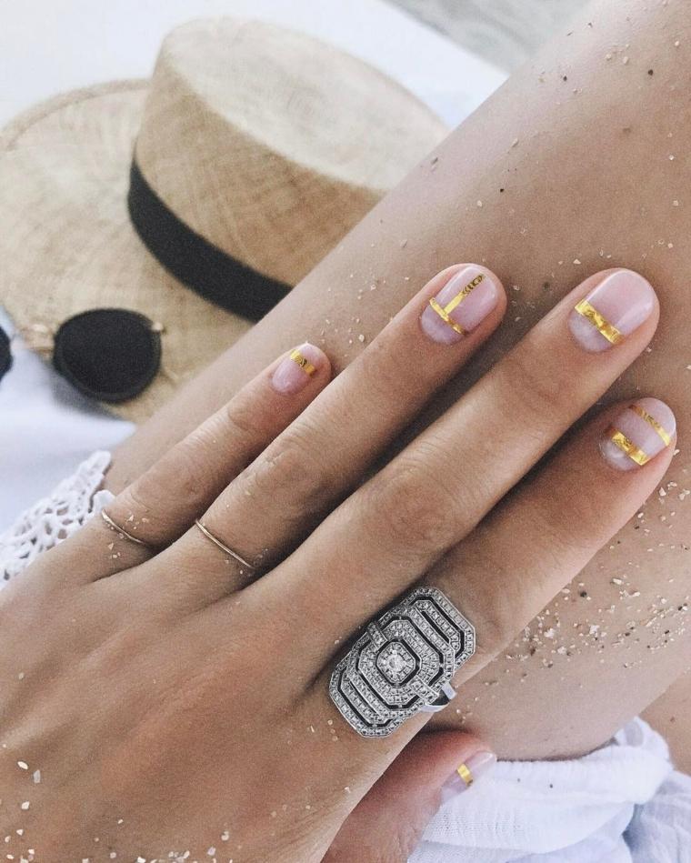 Mano donna con anelli, sabbia sulla gamba, unghie estive, smalto trasparente in gel