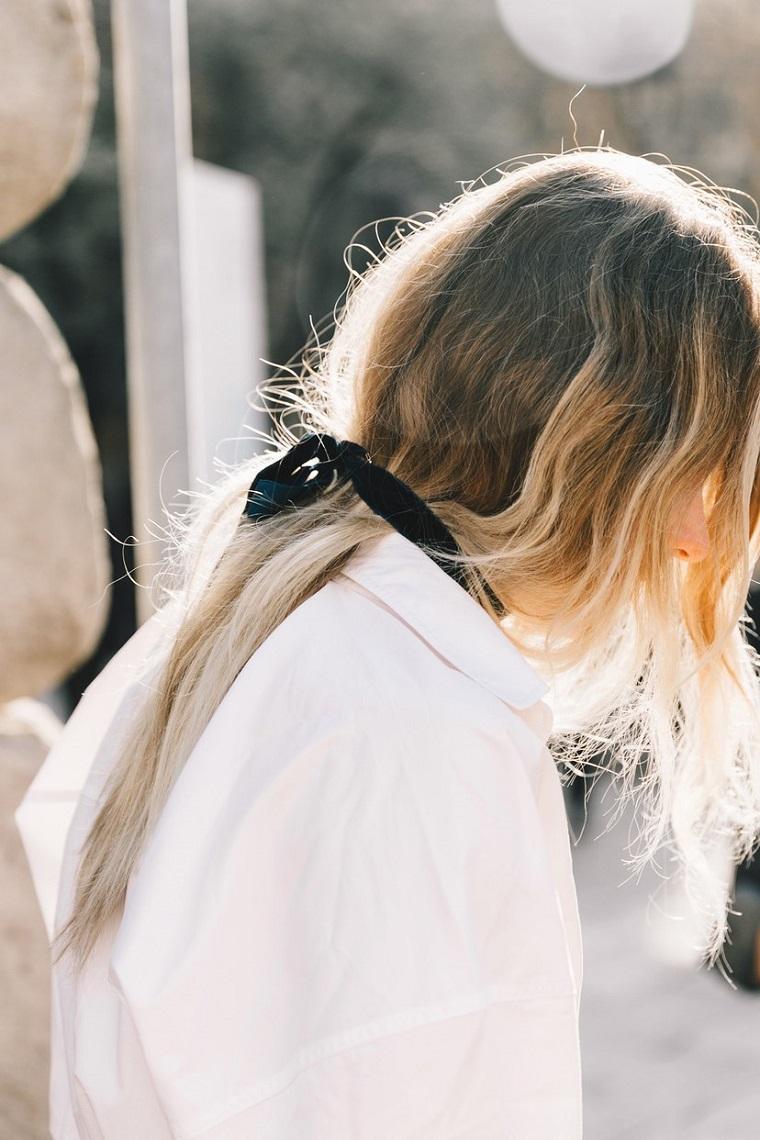Capelli lunghi biondi, coda legata con nastro, pettinature semplici, camicia bianca oversize