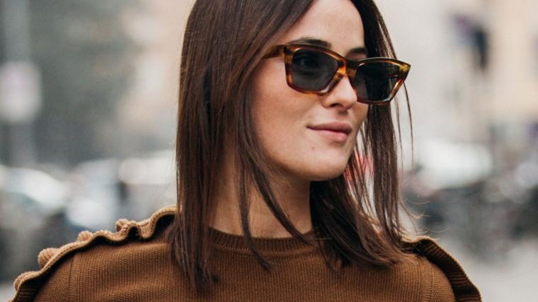 Donna con occhiali da sole, capelli castani mossi, maglione marrone invernale