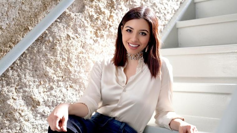 Donna con capelli castani, taglio long bob, abbigliamento da ufficio, camicia bianca e pantalone