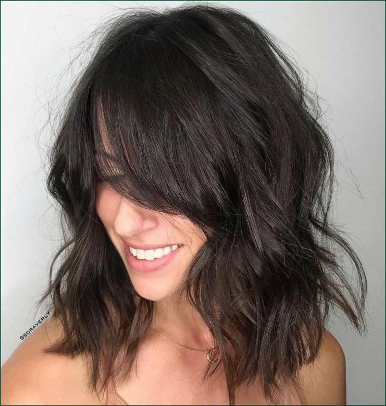 Capelli colore nero, taglio caschetto mosso, acconciatura con frangia, donna sorridente