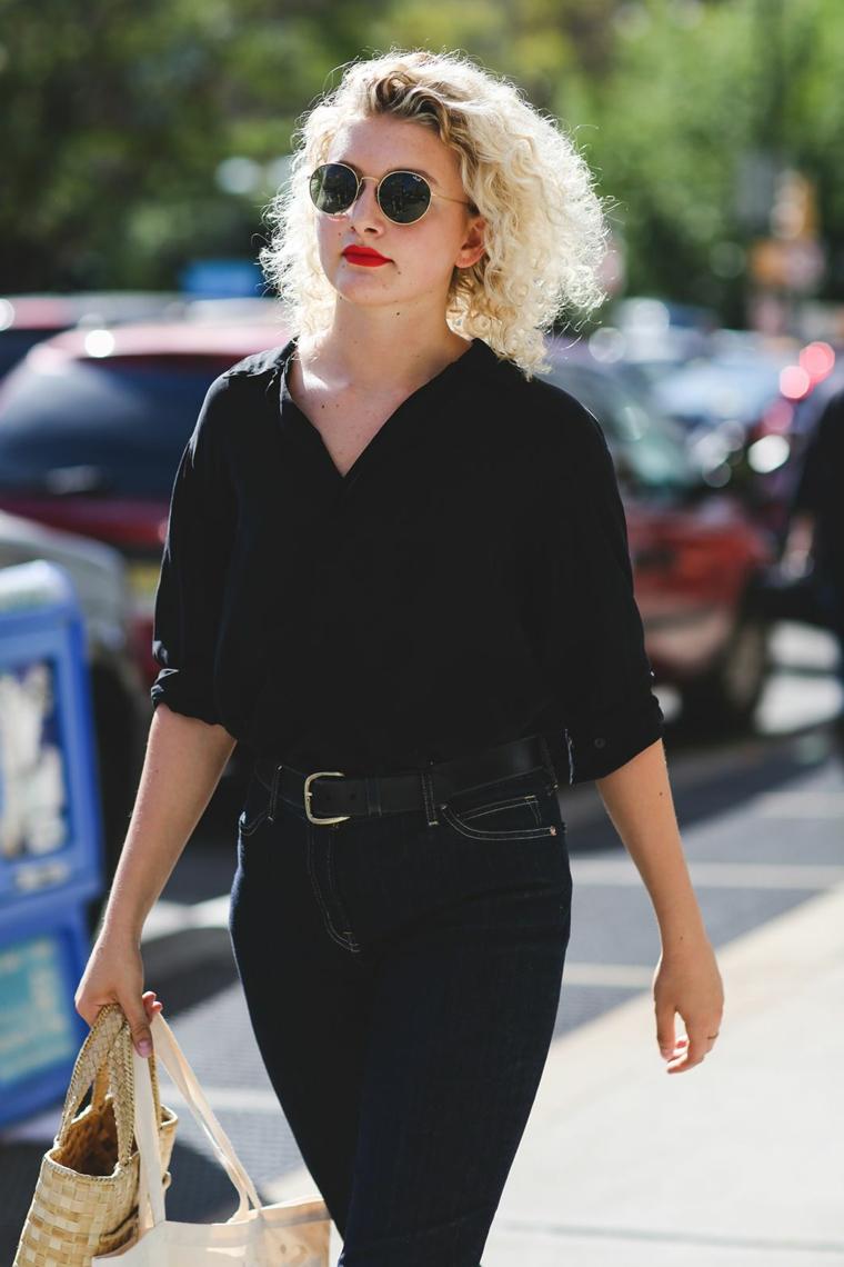 Donna con capelli ricci, colore capelli biondo, abbigliamento casual, camicia nera e jeans