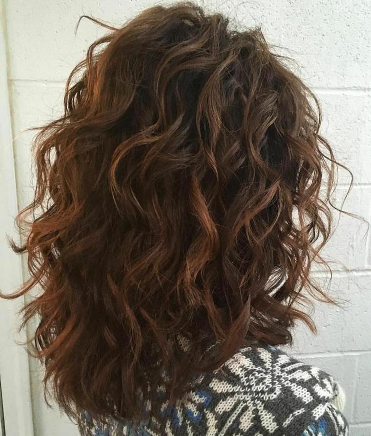 Donna con capelli ricci, capelli di colore castano cioccolato, maglione di lana