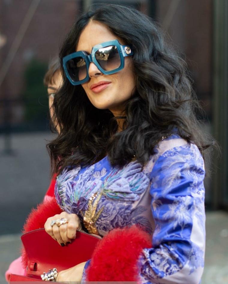 Capelli mossi medi, donna con capelli ricci, occhiali da sole grandi, borsetta colore rosso