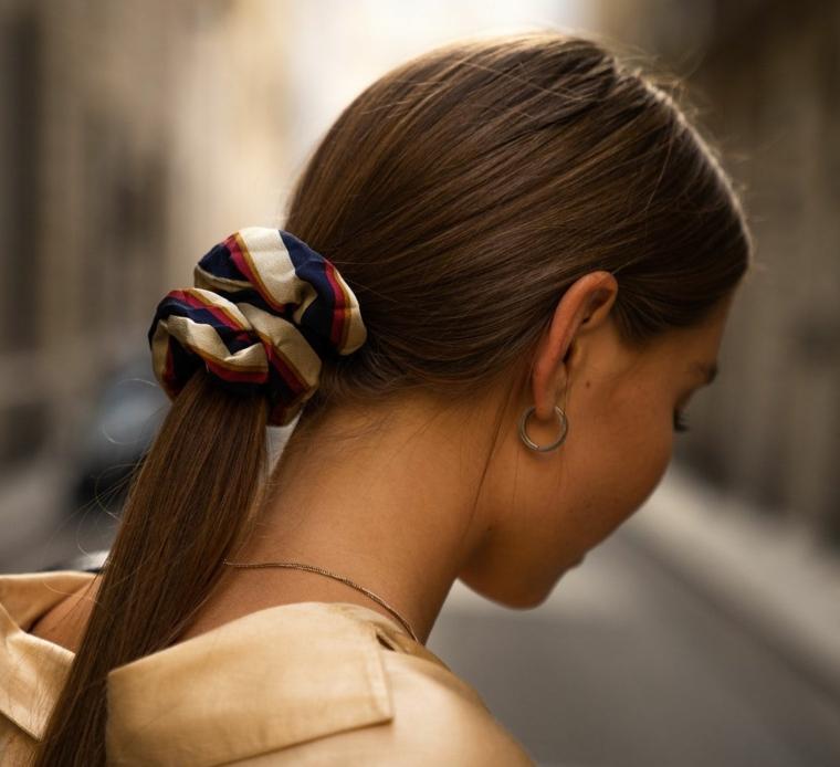 Tagli capelli medi scalati e sfilati, colore capelli castani, coda con elastico