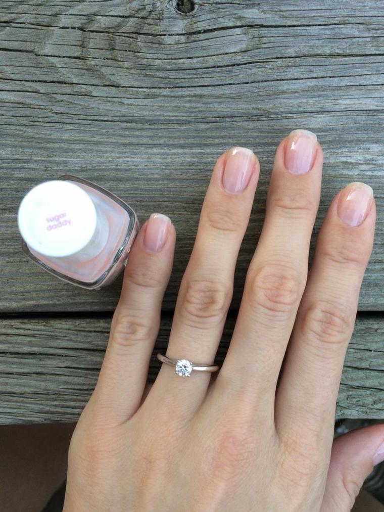 Immagini di unghie con gel, smalto di colore rosa chiaro, tavolo di legno, bottiglietta di smalto