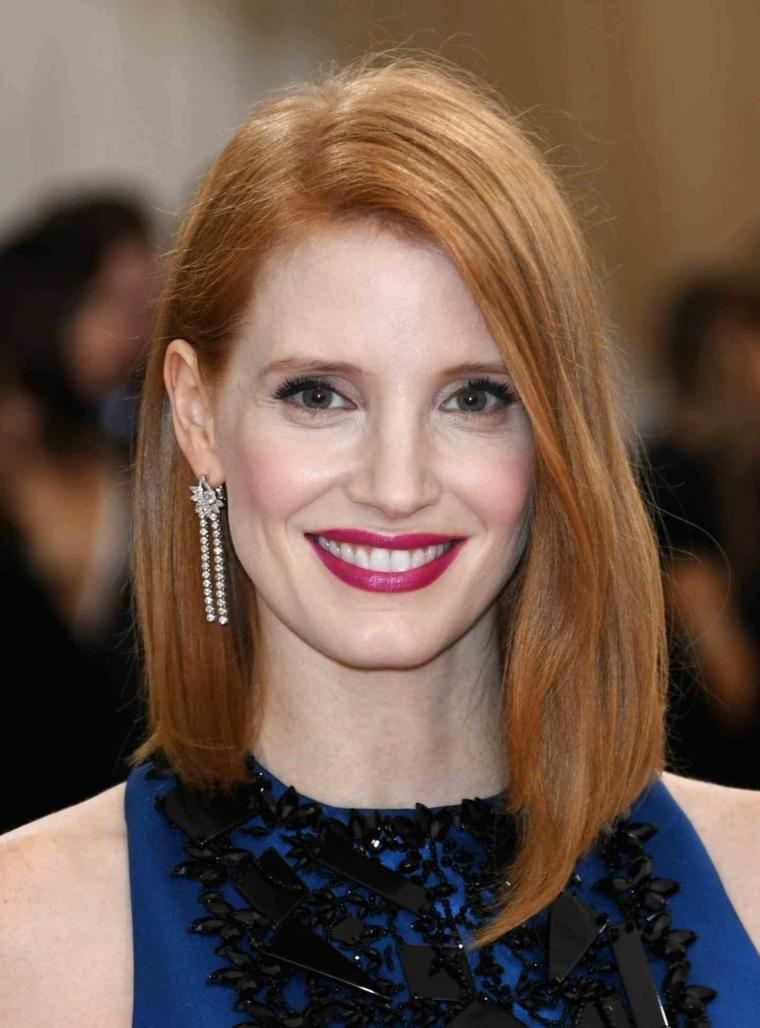 Tagli capelli corti, donna con taglio asimmetrico, colore capelli rosso, rossetto lucido rosso