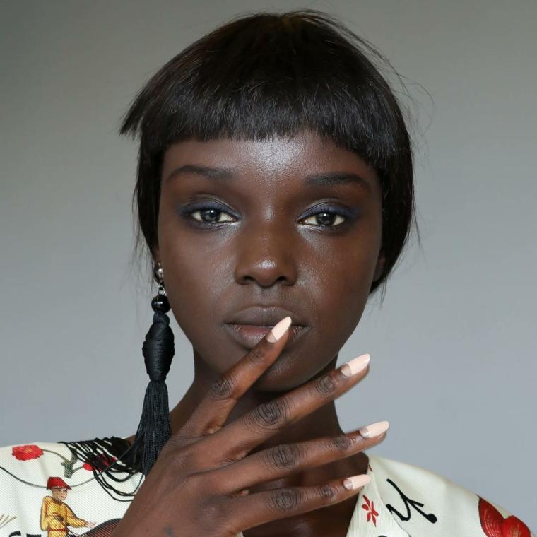 Unghie gel particolari, french manicure inversa, smalto di colore pesca chiaro, donna con frangia