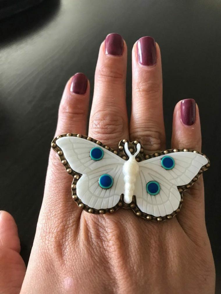 Smalto di colore viola, anello forma farfalla, mano di una donna