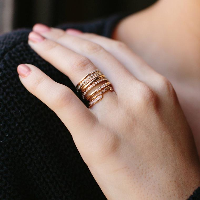 Smalto per unghie rosa, anelli in oro con brillantini, mano sulla spalla, colori estivi unghie