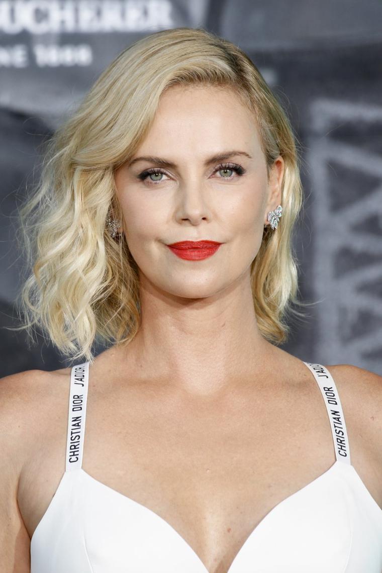 L'attrice Theron, capelli donna bionda, rossetto rosso lucido, taglio scalato medio